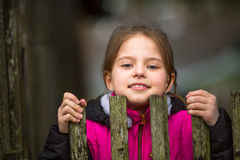 Little girl peeking from behind the fence. Portrait of little girl peeking from behind the fence Royalty Free Stock Photos
