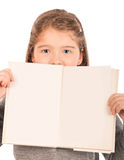 Little girl peeking from behind an open book Royalty Free Stock Photos