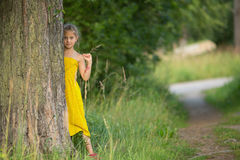 Little girl peeking from behind. The pine trees in the Park Royalty Free Stock Photography
