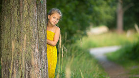 Little girl peeking from behind the tree. Walking. Stock Image