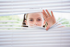 Little girl peeking through blinds Stock Image