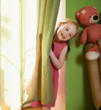 Little girl peeking out from behind curtains Royalty Free Stock Photos