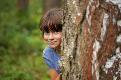 Little girl peeking out from behind a tree trunk. Cheerful little girl peeking out from behind a tree trunk royalty free stock photography
