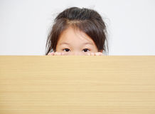 Little girl peeking over table. Portrait of happy little girl peeking over table Stock Image