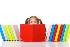 Little girl peeking from pile of books. Isolated Stock Photos