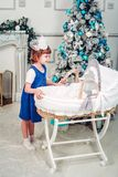 Little girl peeks into the cradle. For Christmas stock photos