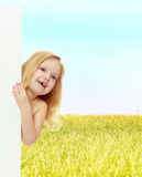 A little girl peeks out from behind the banner. Stock Photo