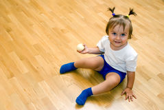 Little girl with peeled apple. Little girl sat on the floor with peeled apple Stock Image