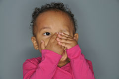 Little girl peeping. Infant mixed race girl covering one eye with her hands while peeping out of the other eye Stock Images