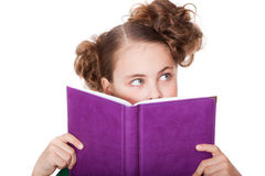 Little girl peeping behind the book. Cute little girl with beautiful eyes peeping behind the book royalty free stock images