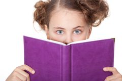 Little girl peeping behind the book Royalty Free Stock Photos