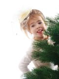 Little girl peeping from behind the branches of Stock Images