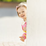 Little girl peeping from behind the wall Stock Photography