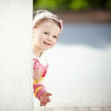 Little girl peeping from behind the wall Royalty Free Stock Images