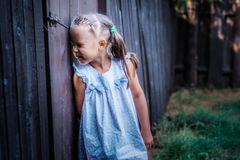 Little girl peeping. Through the fence on the nature stock photos