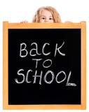 Little girl peeping out a school black chalkboard Royalty Free Stock Image