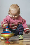 Little girl with peg-top Stock Photos