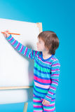 Little girl with pencils at easel Royalty Free Stock Images