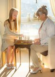 Little girl and pension age woman playing playing chess in the domestic environment. People agains sun light. Educational concept. Little girl and pension age Royalty Free Stock Images