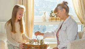 Little girl and pension age woman playing playing chess in the domestic environment. People agains sun light. Educational concept. Little girl and pension age Royalty Free Stock Photography