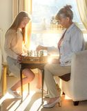 Little girl and pension age woman playing playing chess in the domestic environment. People agains sun light. Educational concept. Little girl and pension age Stock Photography