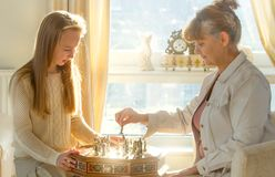 Little girl and pension age woman playing playing chess in the domestic environment. People agains sun light. Educational concept. Little girl and pension age Stock Image