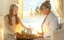 Little girl and pension age woman playing playing chess in the domestic environment. People agains sun light. Educational concept. Little girl and pension age Stock Photo