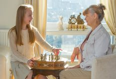 Little girl and pension age woman playing playing chess in the domestic environment. People agains sun light. Educational concept. Little girl and pension age Royalty Free Stock Photos