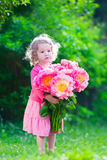 Little girl with peony flowers in the garden Royalty Free Stock Image