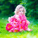 Little girl with peony flowers in the garden Royalty Free Stock Photos