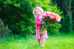 Little girl with peony flowers in the garden stock images