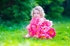 Little girl with peony flowers in the garden stock photography