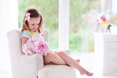 Little girl with peony flowers in white bedroom Royalty Free Stock Photo