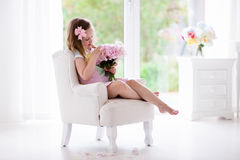 Little girl with peony flowers in white bedroom Stock Photo