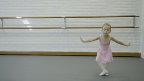 Little girl is performing dancing movements in ballet school. Cute girlie stands and moves actively, with hands and legs, demonstrating techniques of classical stock video