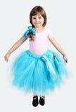 Little Girl Performing in Tutu Skirt. Studio Shot over Grey Royalty Free Stock Image