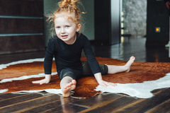 Little girl performs a twine. At home on the floor royalty free stock photography