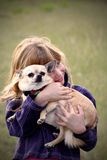 Little girl with pet Chihuahua. A little girl cuddling her pet Chihuahua royalty free stock photo
