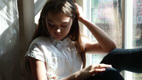 Little girl with pet rat sitting on the windowsill at home