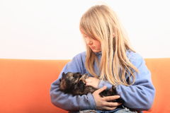 Little girl petting a puppy. Little kid - blond girl in blue pullover holding and petting brown puppy - dog royalty free stock photos