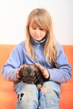 Little girl petting a puppy. Little kid - blond girl in blue pullover and pants with holes sitting on orange sofa and petting brown puppy - dog Stock Photo
