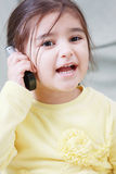Little girl on phone. Little girl in yellow talking mobile phone expressively Stock Photos