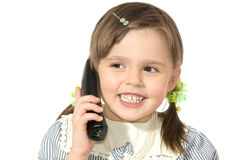 Little girl with phone. The beautiful little girl Speaks by phone and smiles on white background close up Royalty Free Stock Images