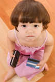 Little girl with phone and baking card Stock Photography