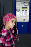 Little girl in a phone box Stock Image