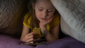 Little Girl With Phone Eat. At night watching cartoons video eating cracker snack lying on the bed with smartphone child little girl caucasian white european 5 stock video