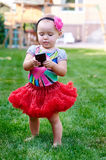 Little girl with a phone in a red skirt Stock Photos