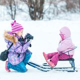 Little girl photographed her sister Stock Photos