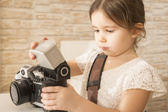 Little girl photographer holding old vintage film photo camera Royalty Free Stock Images
