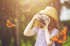 Little girl photographing butterfly Royalty Free Stock Photography